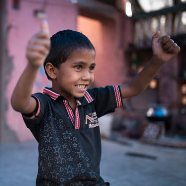 Boy with raised hands and thumbs up