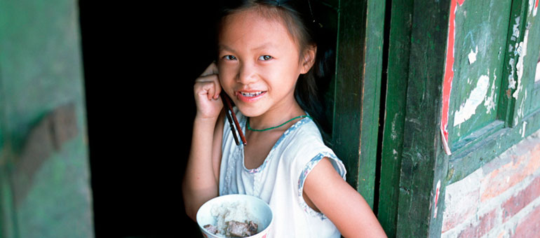 Chinese girl eating from a bowl against green door
