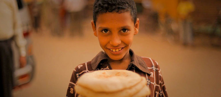 Egyptian boy holding baladi bread in the street