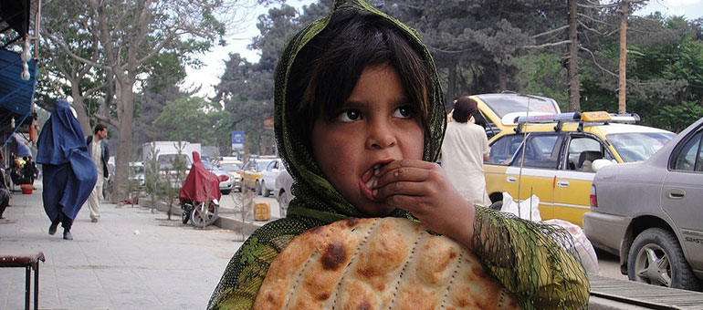 Girl eating bread in the street, Afghanistan