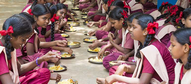 Girls eating in a school in India