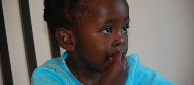 Little girl eating with her hands in Africa