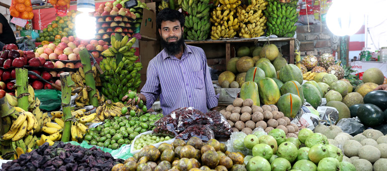 Man selling vegetables in a market in Bangladesh