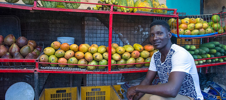 Man sitting in front of boxes of fruits in Tanzania