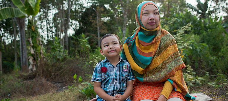 Mother and son sitting on a bench smiling in Indonesia