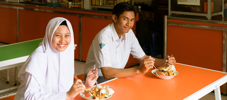 Adolescents eating in their school canteen in Surabaya