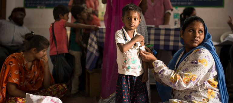 Woman measuring kid arm in India