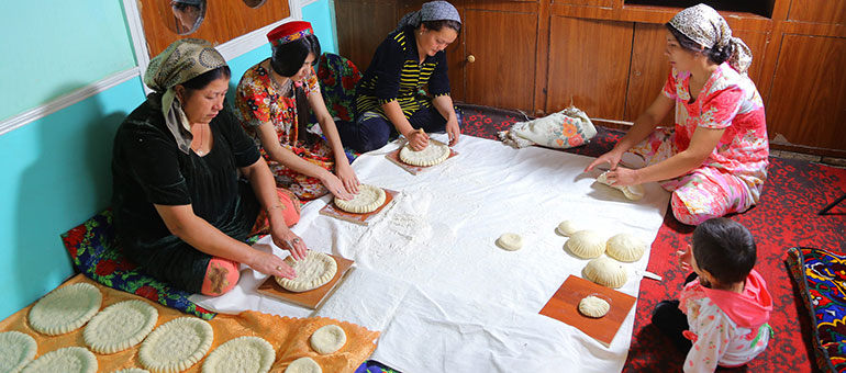Women preparing bread while sitting down in a circle