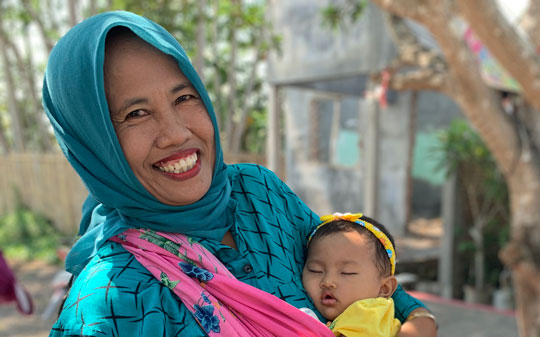 Mother holding sleeping baby and smiling in Indonesia