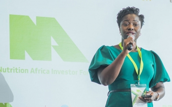 African woman in bright green dress presenting at the Nutrition Africa Investor Forum (NAIF)