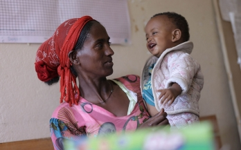 Ethiopian woman holds her baby and smiles at his laugh