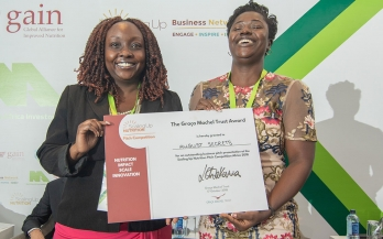 Woman receives a prize for her work in nutrition at the Nutrition Africa Investor Forum (NAIF)