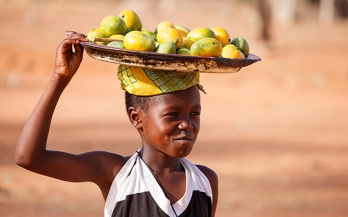 A child carrying fruits in Africa
