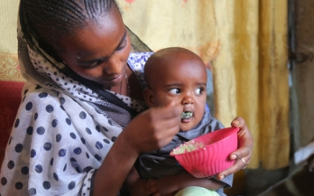 Mother feeding her baby with porridge