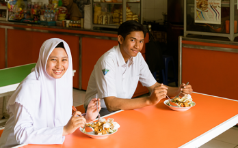 Two adolescents having a meal in school in Surabaya Indonesia