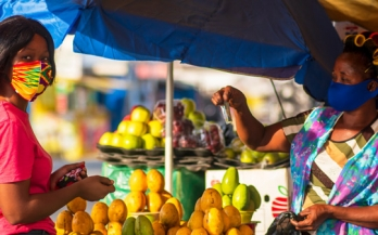 Woman buying papaya from a woman in a street market ion Africa both wearing colorfuls masks