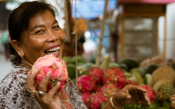 Woman holding a dragon fruit and smiling