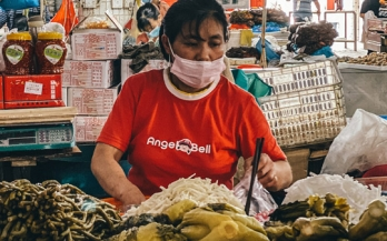 Woman wearing mask while sorting food in a market