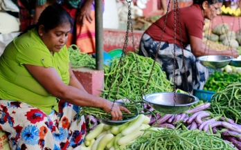 Two women weighting vegetables in the market