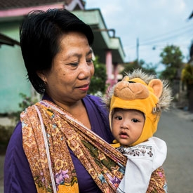 Woman holding baby with lion hat