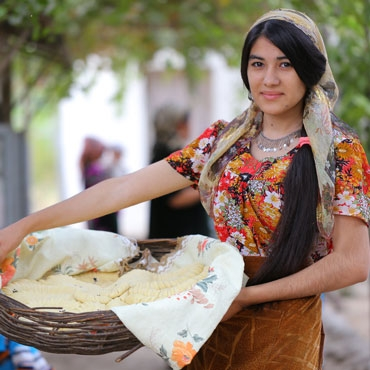Tajikistan girl holding basket with bread