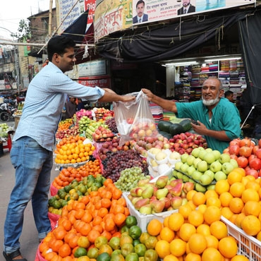 Man buying fruits from a market seller in Bangladesh